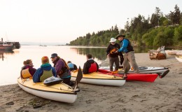 Two guides help a group of novice kayakers prepare to launch their boats